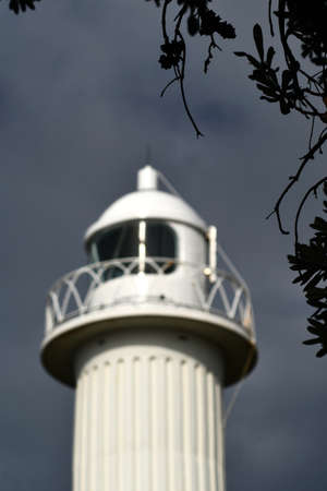 A white light house is seen against a dark sky. The focus is on the foreground, but the the light house sparkles in the sunlight. Silhouettes of leaves frame the view. Stock Photo