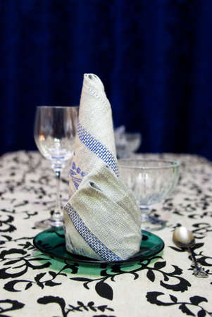 elevenses: Formed serviette on a plate with wine-glass on background Stock Photo