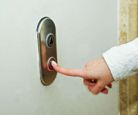 pressing: Woman pressing elevator button to go down