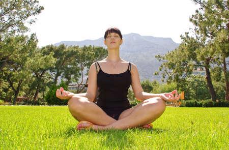 Jonge meditating vrouw zitten op gras  Stockfoto