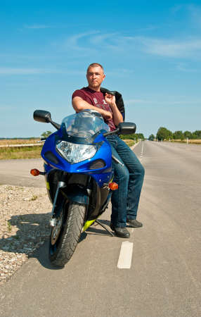 empty road: Resting biker with motorcycle on empty road Stock Photo
