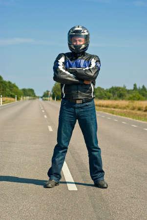 motociclista: motociclista de pie en el centro de la carretera vac�a