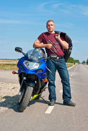 Motorcyclist posing near his motorbike photo