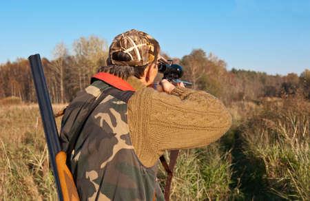 Hunter gericht met telescoop bezienswaardigheden op geweer Stockfoto