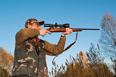 old rifle: Hunter aiming mooses with telescopic sights on rifl