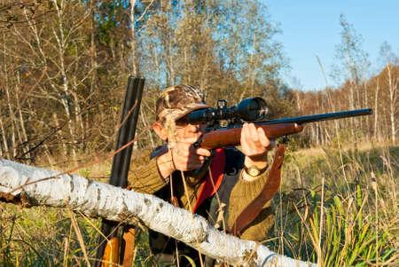 Hunter aiming animals with rifle near fallen birch