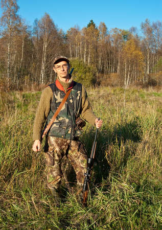 Hunter posing with rifle in nature photo