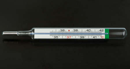 analogue: Analogue thermometer over black Stock Photo