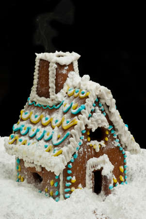 Gingerbread house with a lot of snow at night with smoke from chimney photo