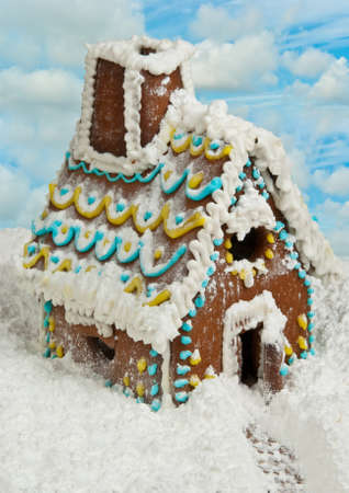 Homemade gingerbread house with cloudy sky on background photo