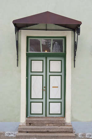 Green door with roof over stairs photo