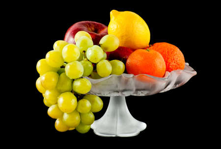 Fruits in glass vase isolated on black photo