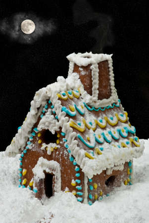 Gingerbread house at night with moon on sky photo