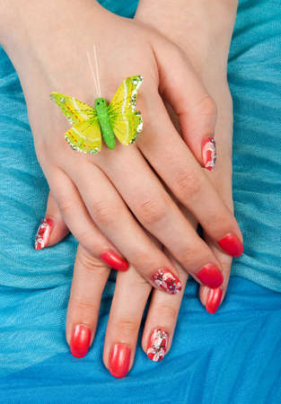 Woman hands with manicure and nail painting after SPA over blue background photo