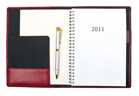 Open diary for year 2011 and pen over white photo
