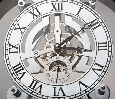 Con números romanos y engranajes visibles del mecanismo del reloj