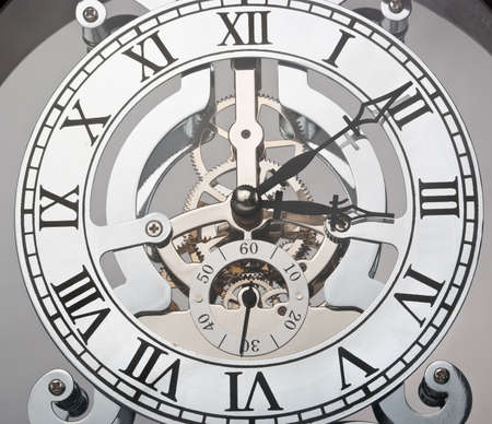 Clock with roman numbers and visible gears of  mechanism