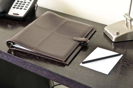 Brown leather paper folder on desk photo