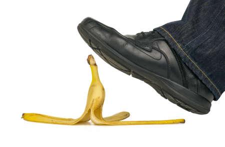 Man stepping on banana peel isolated on white photo