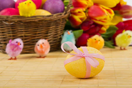 Easter egg tied up with ribbon with basket and tulips on background photo