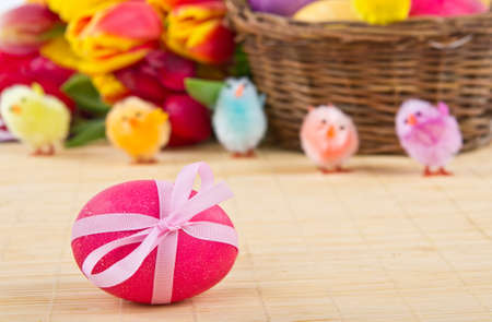 Pink easter egg with bow on bamboo mat photo