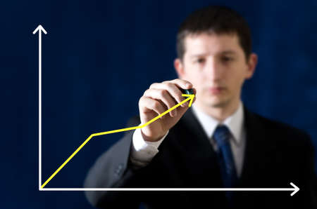 Businessman drawing chart describing growth of market photo