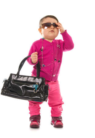 Baby girl model in pink with sunglasses and hand bag isolated on white photo