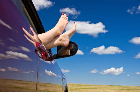 Woman legs out of car window with blue sky on background