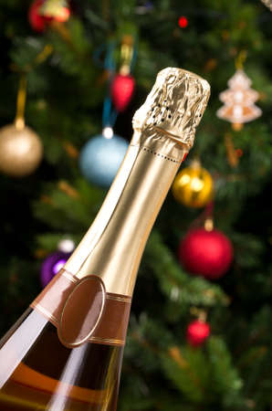 unopen: champagne bottle with decorated christmas tree on background. Stock Photo