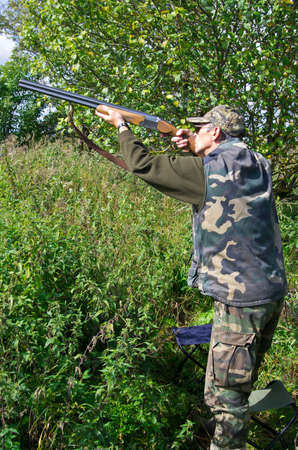 Mature hunter shooting pigeons with shotgun photo