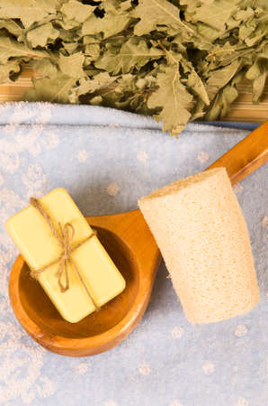 Sauna wooden spoon and soap on towel photo
