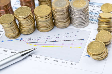 statistical: Columns of coins and pen over business statistical chart Stock Photo
