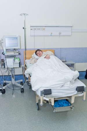 Mujer joven en la sala del hospital y el seguimiento de equipos médicos Foto de archivo