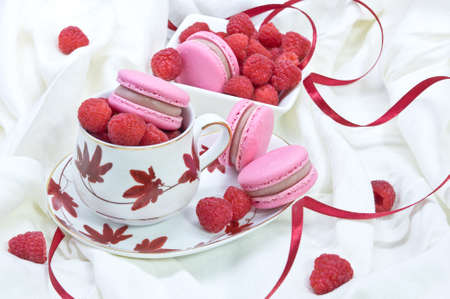 Teacup and bowl full of fresh raspberries and pink macaroon cookies