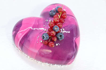 Mousse cake in shape of heart with mirror glaze decorated with blueberry and red currant Stock Photo