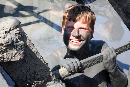 A man laughs while uphill in a therapeutic mud lake