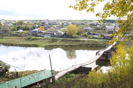 ural: A wide river divides the city into two parts. On both sides of the river there are houses and a forest