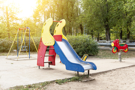 Childrens playground in the courtyard of the house (swings, slides). Bright, juicy photos of a childrens playground in the courtyard of a residential building. Children swing, carabolic, roller coaster, atractions. Stock Photo