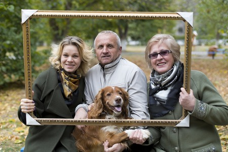 aging face: The aged husband with his wife, daughter and dog are photographed in autumn