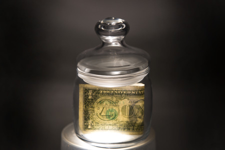 avarice: Dollar in glass jar A one-dollar banknote is a jar with a backlight
