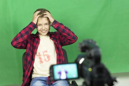 緑の背景にビデオ少年ブロガーを記録します。男の子のブロガーは、自宅ビデオ カメラに緑の背景にビデオを記録します。ブロガーはラップトップ 写真素材