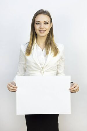 Girl with sheet of paper A3. Business girl holding a clean sheet of paper A3. Write your text, advertise your services.