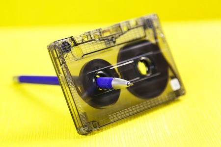 Audio cassette and pencil. Music of the past. Audio cassette with music of 80 years and a pencil for rewinding tapes of tape on a yellow background Stock Photo