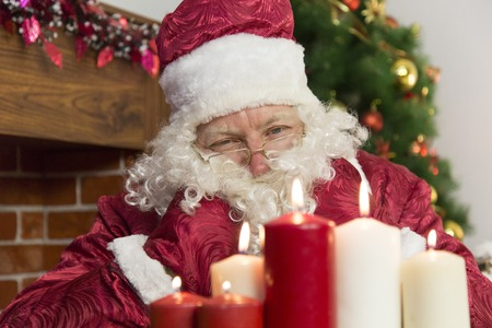 grandfather frost: At Christmas, Santa Claus lit candles on the background of a fireplace and a Christmas tree.