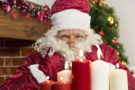 At Christmas, Santa Claus lit candles on the background of a fireplace and a Christmas tree.