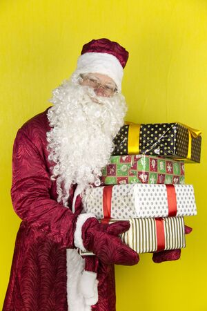 Santa Claus with gifts. Cheerful Santa Claus holds gifts in hands on a yellow background. Stock Photo