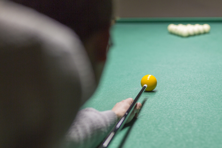Billiards close-up on the green. Hands of a man holding a stick for playing billiards and aiming at the sharar on the table Banque d'images