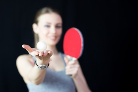 Bella ragazza con una racchetta da tennis e una palla. L'atleta tiene in mano una racchetta da ping pong e una palla.