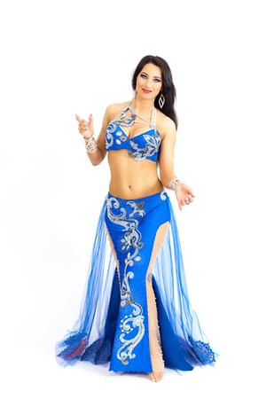 Una joven bailarina vestida de azul realiza una danza oriental del vientre. Aislar. Hermosa chica en ropa nacional brillante bailando sobre fondo blanco. Foto de archivo