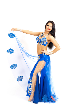 Una joven bailarina vestida de azul realiza una danza oriental del vientre. Aislar. Hermosa chica en ropa nacional brillante bailando sobre fondo blanco.